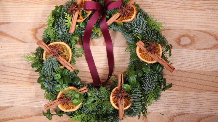 Mette Blomsterberg pynter sin grønne granbarkrans med saker fra kjøkkenet: appelsinskiver, kanel og stjerneanis.