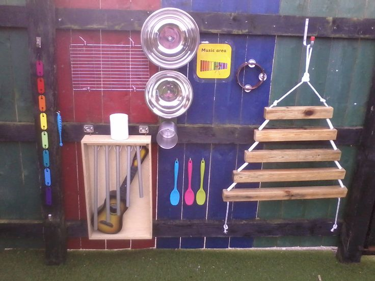 EYFS outdoor provision - music area - stainless steel mixing bowls make a bell like noise - old xylophone dismantled and strung into a chain using cable ties and stretched taught using 2 hooks - old wind chimes suspended on string and hung in a box - wooden xylophone was once a bunkbed frame - cooling rack cable tied to the fence - silicone rubber spoons for beaters (not too noisy!) - and plastic ukulele because they all want to play mine!