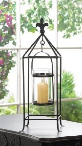 Oh la la! Candlelight with a touch of European flair is a surefire way to amp up the style in your room. This metal candle stand features a black rod framework topped with a fleur-de-lis finial. Inside, a clear glass candle cup hangs from a simple metal frame that will let the light shine bright. http://www.wholesalemart.com/Wholesale-Candle-Holders-s/85.htm