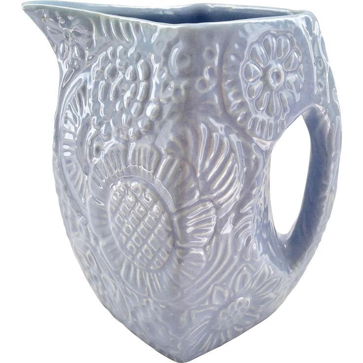 This beautiful Niloak Pottery blue pitcher with embossed flowers was made in Benton, Arkansas. The four-sided geometrical pitcher is a true work of
