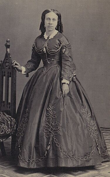 Portrait of a woman wearing a dress with incredible braiding/embroidery designs, ca. 1850-1865.