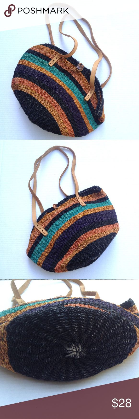 """Ghana colorful woven shoulder market tote shopper Made in Ghana, this colorful market tote is made of naturally dyed woven elephant grass and leather. Genuine raw leather straps have a strap drop of 11.5"""". Bag measures 16"""" long, approx. 6"""" wide (sides expand) and 11"""" tall. Some light wear on bottom from use (see pics), otherwise EUC. Carved button and leather thong closure. Colors of bands include black, purple, teal and two shades of orange. Feel free to ask questions! Ghana Bags Totes"""
