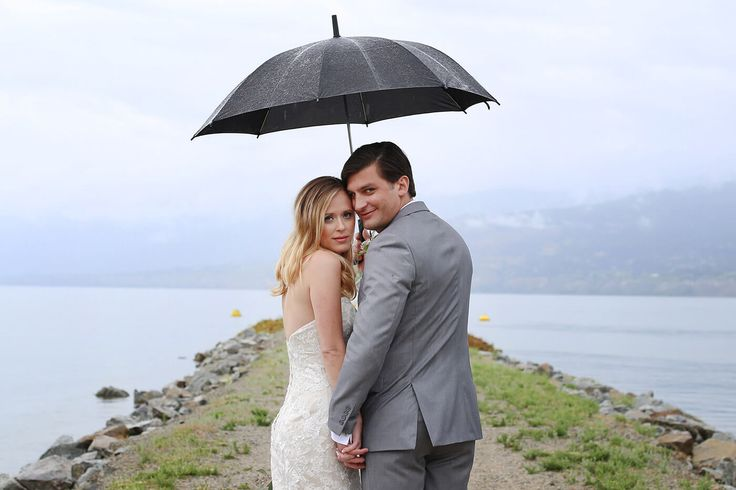 Bride and Groom shelter under a sombre black umbrella, as they walk out on the rock groin, towards the water. Photography: Something Blue. Location: Beside the SS Sicamous Stern Wheeler, on the southern shore of Okanagan Lake (British Columbia, Canada)