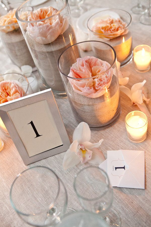 Jenny-- Changing my centerpieces to this: the shells inside the vases with a garden rose on top, instead of those thick candles.. The florist will line the aisle with them, and then move them to the tables for centerpieces. We will still be using the baby food jars, though, so keep making 'em! ( I need to send you the lace!)