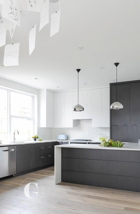 Modern black and white kitchen features white flat front upper cabinets and black flat front bottom cabinets paired with white quartz countertops and a glossy white grid tile backsplash. like - the grey, and floorboards dislike - lights