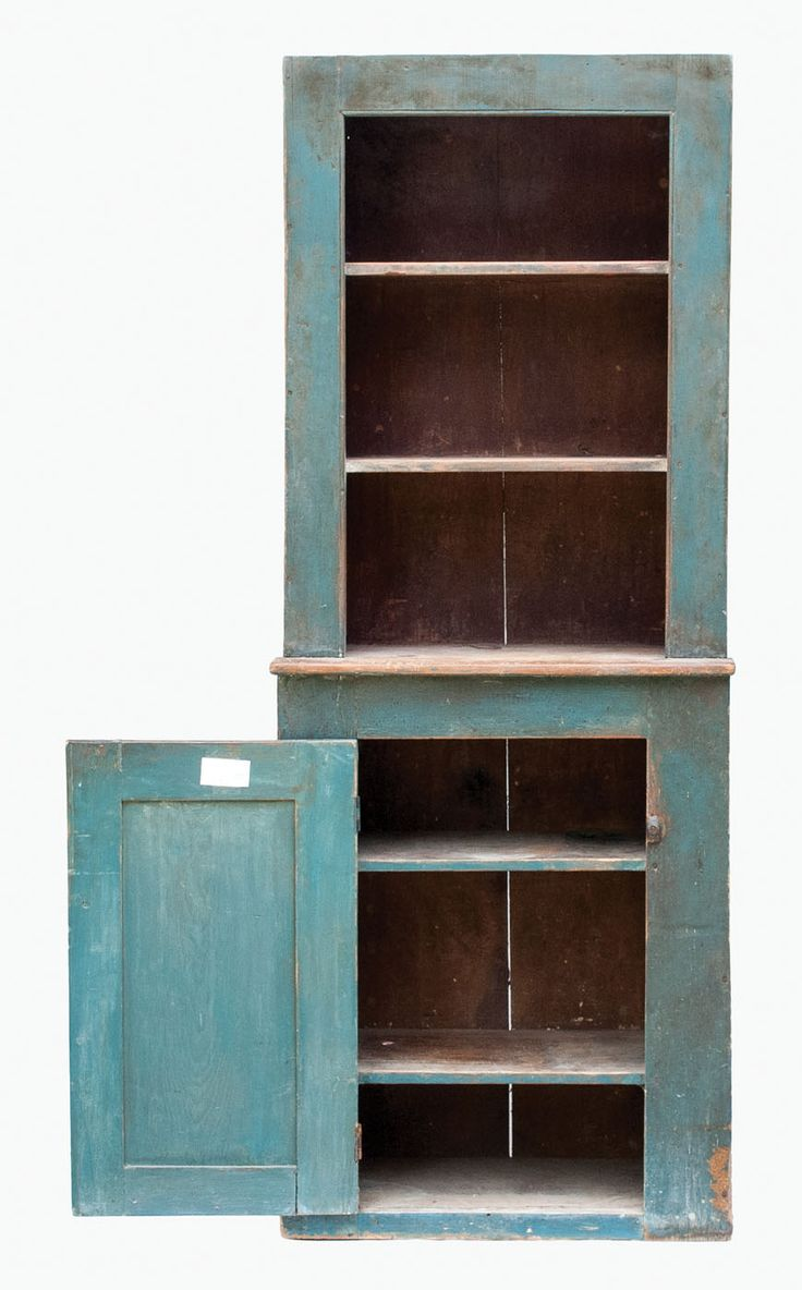 """Lot 120: 19th C. Stepback Cupboard New Hampshire, pine, in early light blue painted finish, appears to have been cut at the stepback, three-shelf open top with plate rails, three-shelf base with raised panel door, wood twist door closure, tagged on inside of door by Ed Clerk """"19th c. New Hampshire step back cupboard in original paint"""", wear appropriate to age with patina, (Ed's cat bit bottom right corner), 6' 3 1/2″ h, 29 1/2″ w, 14 1/2″ d, (ex. Ed Clerk collection)."""