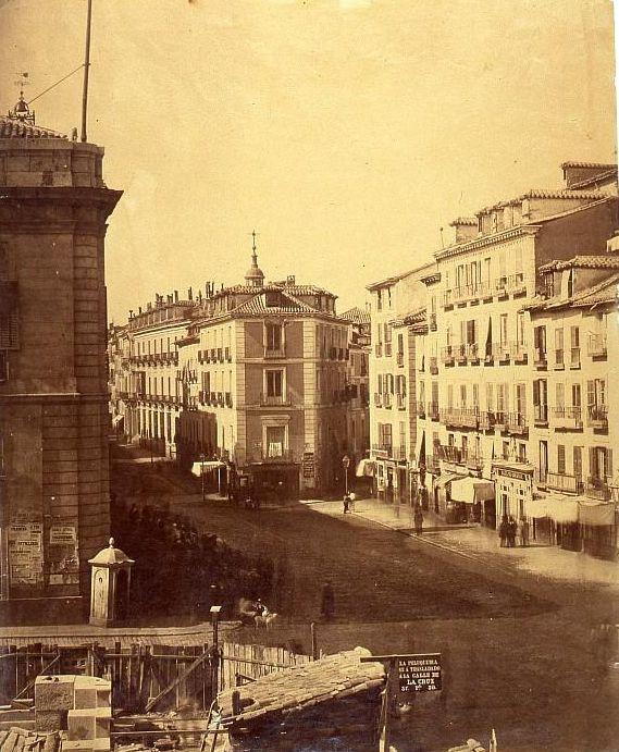Puerta del Sol  antes de la reforma que comenzaría en 1857  Ch.Clifford. Museo de Historia (Madrid)     --  Un ángulo diferente al de la foto anterior. Ésta está tomada cuando ya se había derribado la Iglesia del Buen Suceso y había comenzado el de otros edificios, como por ejemplo, el que hace esquina con Carretas, rodeado por una valla en la imagen.