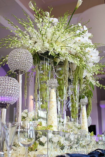 Crystal candle holders and tall vases full of flowers