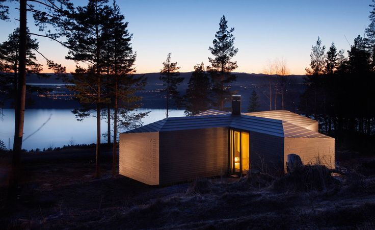 Cabin in the Krokskogen forest by Atelier Oslo. The irregular shape was created in response to the harsh environment. In order to resolve the issue of windy conditions, the house was based on a cross plan, which formed a number of exterior hideaways. The structure was created by using prefabricated elements, which were assembled on the site.