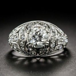1.02 Carat Art Deco Diamond Ring: Both Edwardian and Art Deco design elements artfully coalesce in this singular and stunning vintage engagement ring, die-struck, hand-pierced and hand-finished in platinum - circa 1920s. The gently domed, diamond-studded ring is crowned with a gorgeous, bright white, ultra-sparkling European-cut diamond, weighing 1.02 carats. #langantiques #artdeco