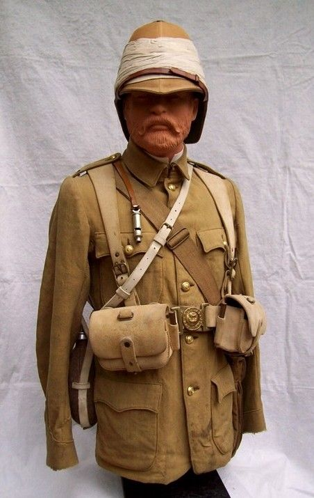 Grenadier Guards Officer's serge frock. This serge frock bears evidence of a rough campaign life with its numerous field repairs and staining. The sleeves are lined in a lightweight flannel for additional warmth. He wears the pattern 1888 Valise braces and belt with Mk.3 ammo pouches.