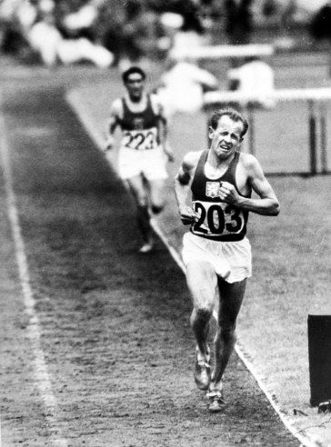 """Caption from LIFE. """"Distance champion Emil Zatopek of Czechoslovakia, running with his characteristic agonized expression and no grace, starts last lap in 10,000 meters, where he set a new Olympic record. He received a gold medal and promotion from second to first lieutenant in Czech army."""""""