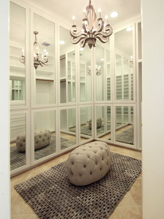 Chic closet with floor to ceiling mirrored closet doors and travertine tile closet floors. Closet with lush gray area rug, tufted gray oval ottoman and modern antiqued mirror chandelier.