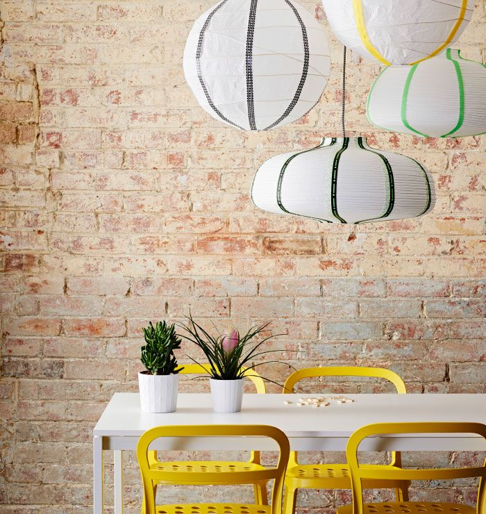 Decorated VÄTE lamps hang above white dining room table and yellow chairs.
