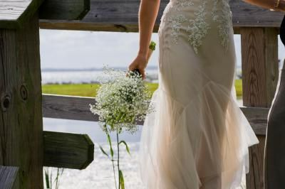 This beautiful bride is carrying delicate baby's breath in Corolla, North Caroline. #DestinationWedding