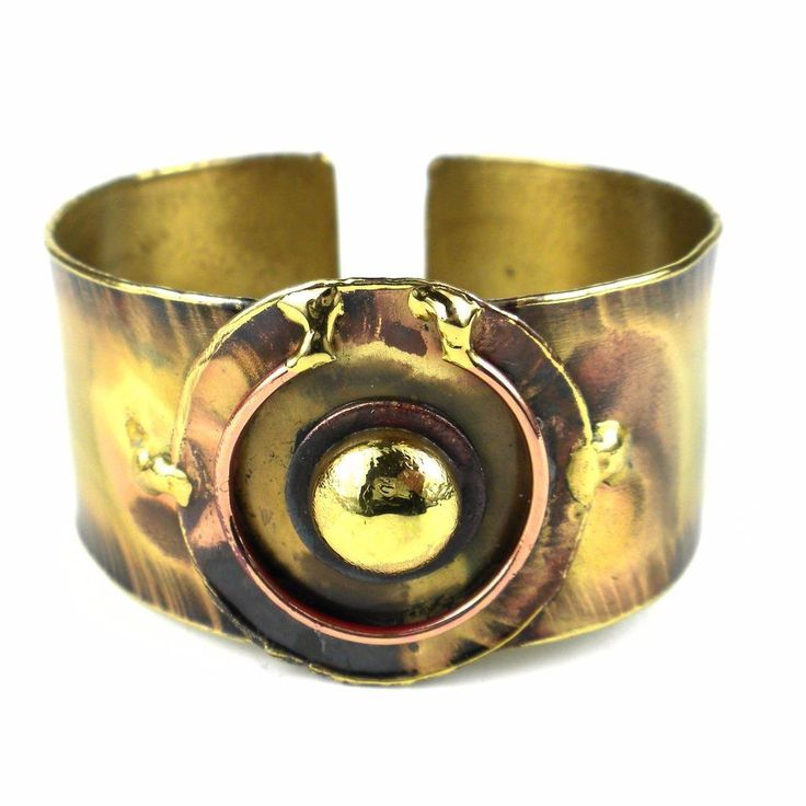 Handcrafted by South African artisans, this feathered brass cuff features a copper and brass center piece. The feathering and color on this 1.1-inch wide bracelet is achieved by applying extreme heat rather than paints or dyes.