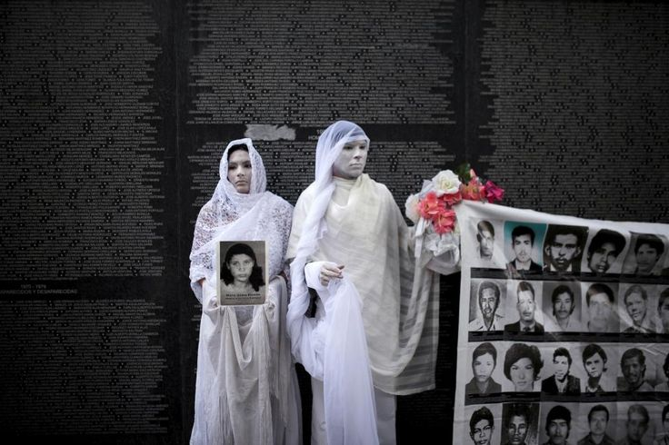 Performers stand in front of a monument for people who disappeared during the Salvadoran Civil War, in Cuscatlan Park in San Salvador May 26, 2015. Relatives of those who disappeared and victims of the civil war participated in a memorial service for these people and for the prisioners of war, according to organisation Comite Pro Memoria Historica. REUTERS/Jose Cabezas