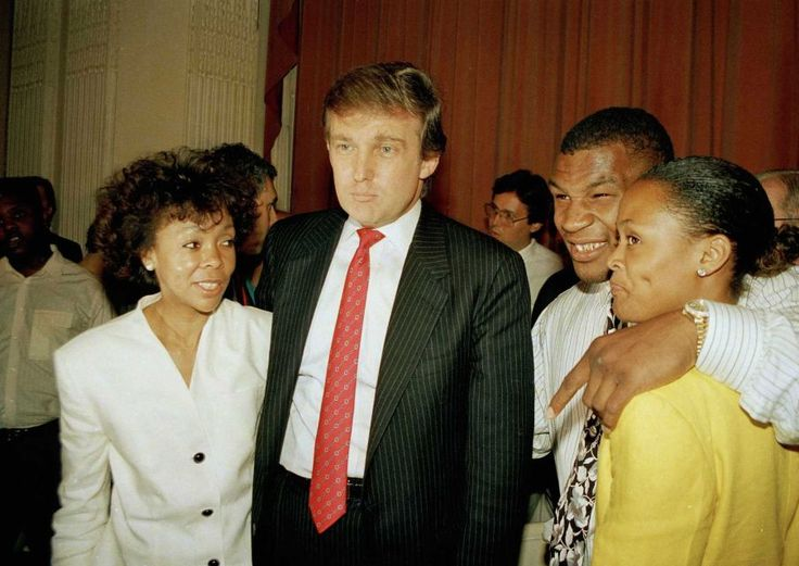 """Heavyweight champion Mike Tyson puts an arm around his wife Robin Givens as her mother, Ruth Roper, left, looks on accompanied by real estate tycoon Donald Trump at a news conference in New York, July 12, 1988. The fighter said his previously announced """"retirement"""" would last only one or two months while he also revealed that he is being advised by Trump and that his trainer, Kevin Rooney, may be on the way out."""