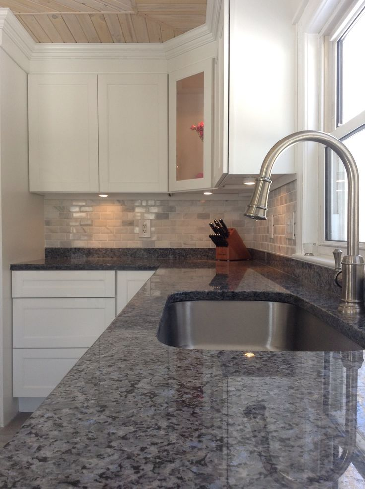 Blue pearl counters.. Artisan faucet , white marble subway tile backsplash , white cabinets.. All that is missing is
