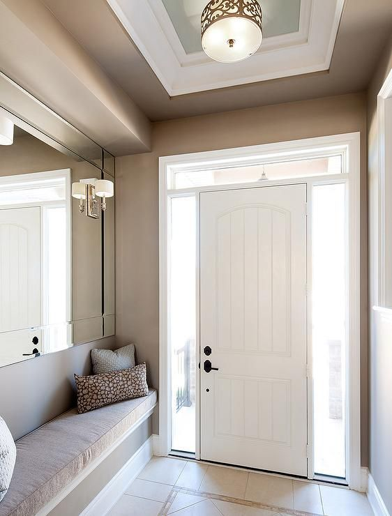 Chic, long foyer features walls painted taupe lined with a long built in bench under a full length mirror illuminated by sconces.