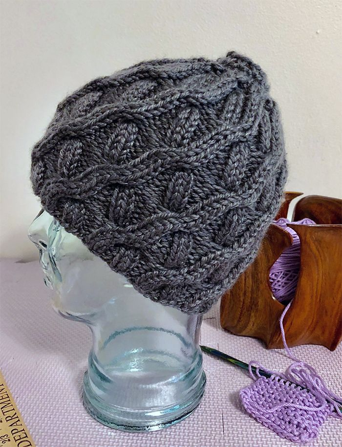 Free Until Jan 31 2018 Knitting Pattern for Slope Side Messy Bun Hat -  A messy bun hat with a unique cable pattern that gently slopes up and around the hat. Bulky yarn. Designed by Cheryl Beckerich
