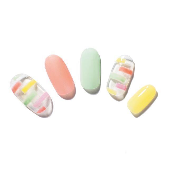 キャンディみたいなジオメトリックネイル 互い違いのボーダーがユニークなジオメトリックをキャンディカラーで表現。透明度の高いカラーを選ぶことで、ポップに転びすぎない。小指にイエロー、中指にミントグリーン、人さし指にオレンジのジェルを二度塗りして。親指と薬指は、クリアのジェルをベースに塗り、その上から、オレンジ、イエロー、グリーン、ピンクのジェルを細い筆にとって、線を引いていく。