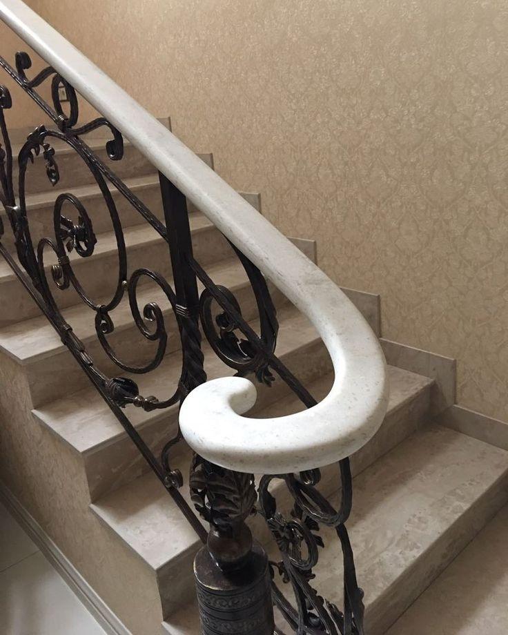 Белые перила лестницы из искусственного акрилового камня. Кованная лестница в доме. Ступени из искусственного акрилового камня, имитация натурального камня. Дизайн дома, интерьера, лестницы.