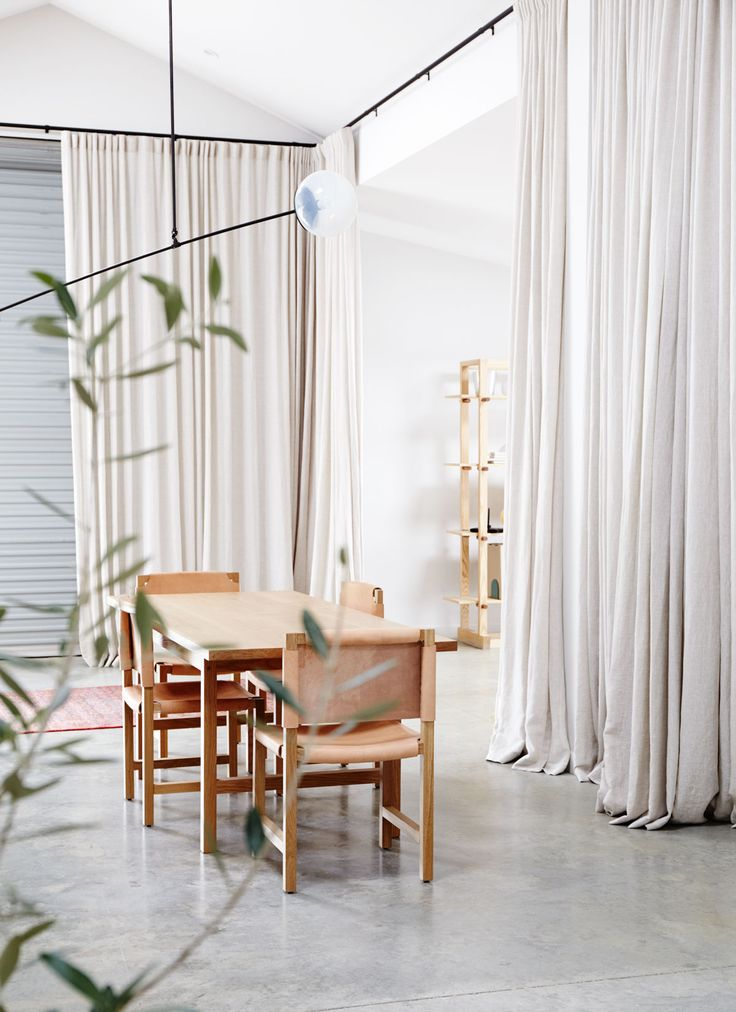 """Sheer linen drapes add to the home's movable, transformative appeal. """"In the evenings, we close them all up and the space around the dining table becomes very intimate. It's lovely in winter,"""" says Dowie. """"Then, when we need to, we can open everything up again. Paul and I always dreamed of living in a warehouse or loft apartment, and this is our version of that. It's our ground floor loft—in New Zealand, in a barn."""""""