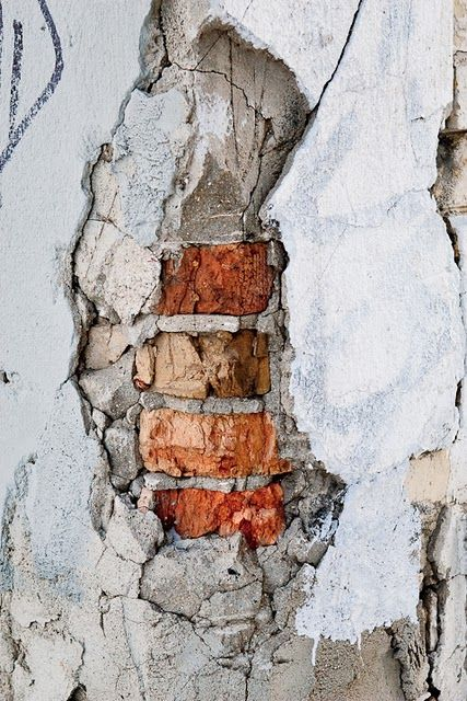 The plaster crumbles to reveal bricks and mortar that hold stories of their own.