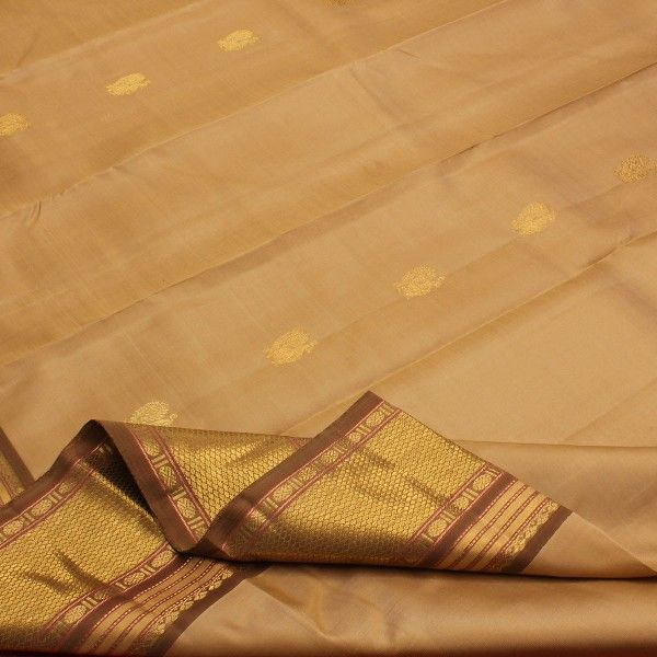 Ripples and swirls of iced cappuccino create a creamy #silk sari, dotted with gold peacock motifs on the body. The border in coffee and cinnamon, is worked in zari with honeycomb pattern and rudraksh motifs. Slender red threads add a hint of colour. The heavy gold and brown pallu boasts of traditional motifs like yalis and elephants. The plain golden blouse with running border completes this Sarangi Creation. View this sensuous beige collection at #Sarangi. Code 580125962.