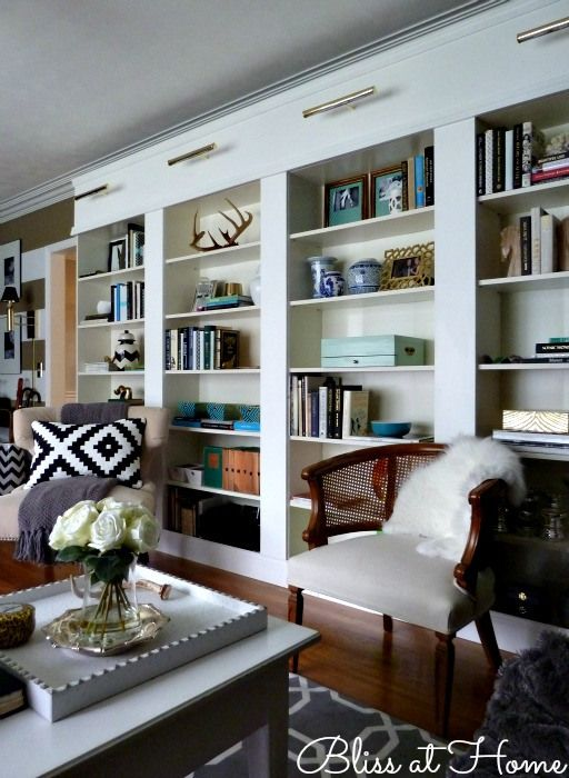 Ikea BILLY bookcase HACK via Bliss at Home... Library wall made to look built in complete with brass lighting and a hidden sound system.