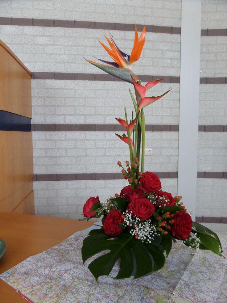 Met Heiliging de wereld in     De kleuren RoodGeelOranje staan voor Vuur!! Witte bloemetjes, het nieuwe leven door de Heilige Geest.     Er verschenen aan hen een soort vlammen,   die zich als vuurtongen verspreidden   en zich op ieder van hen neerzetten,   en allen werden vervuld van de heilige Geest.                                         (Handelingen 2: 3-4a)    Rode roos -  Liefde, lijden, offer. Wit -  Feest, vreugde, waarheid, reinheid. Geel/Oranje -  Licht, luister, glorie.