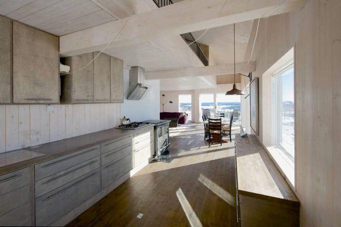 ÅPEN LØSNING: Kjøkkenet, som eieren selv har tegnet, er plassert sentralt i hyttas hovedrom, og slik at skap og hyller tar minimalt med plass. Interiøret er minimalistisk, og dagslyset får flomme inn via den lange vindusrekken. Hemsavdeling er like under mønet og luke til frostfri kjeller i kjøkkengulvet. © Nils Petter Dale