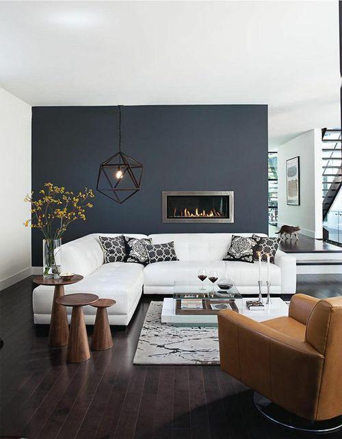 sofá branco na decoração da sala de estar com parede preta, almofadas escuras, poltrona de couro e conjunto de mesas laterais de madeira, piso de madeira