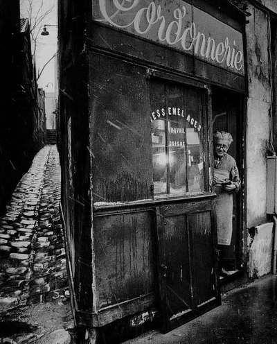 DOISNEAU -Le cordonnier de la rue Pixéricourt - PARIS - 1974