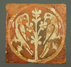 Medieval floor tile from Tintern Abbey. This item comes from: National Museums & Galleries of Wales (Item reference: 32.376/51). This tile, produced between 1272 and 1300, shows two birds feeding from a central tree. Tile size: 135 x 136mm.
