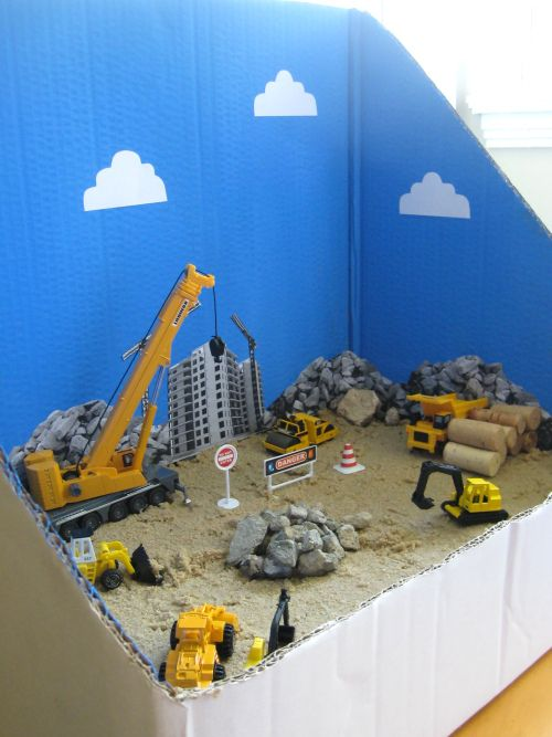 construction site small world play - love the cardboard divider (it will help my kiddos keep the pebbles/sand in