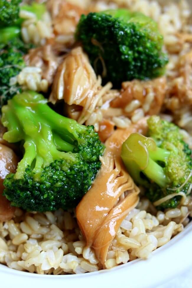 Instant Pot Chicken Broccoli Rice Bowl--brown rice is topped with a savory sauce, tender pieces of chicken and barely cooked broccoli florets.