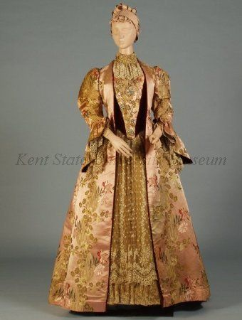 """1890s Teagown of velvet and brocade. Label: """"C. Worth, Paris."""" The overdress of deep red velvet, pink floral brocade, and same brocade in salmon ground. The open dress with puffed sleeves and large ruffled cuff lined with velvet and trimmed with lace """"engagents."""" The sleeveless under dress with red velvet bodice, stand-up collar of lace over satin, and ruffled falling 18th century style cravat."""