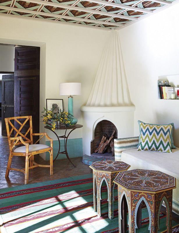 Sala con techo de bambú con toques turquesa y chimenea tradicional marroquí, revestida de cal.