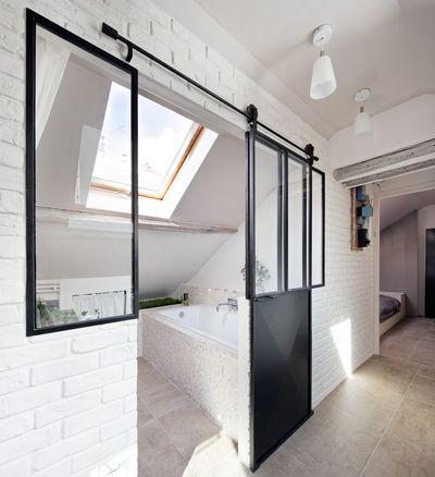 La salle de bains est séparée par une verrière atelier. Beautiful light-filled bathroom with sliding steel door.