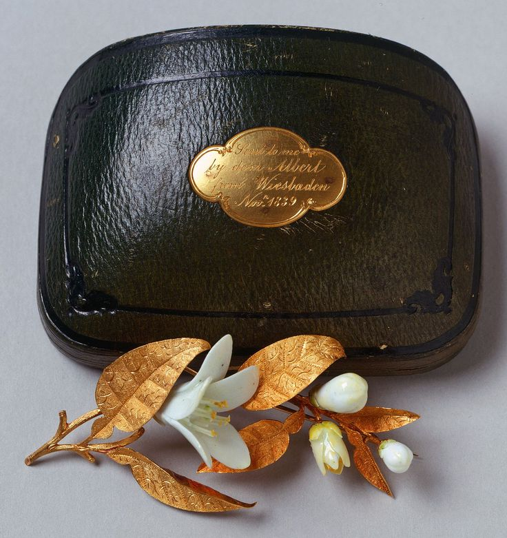 Orange blossom brooch, gold & white porcelain, 1839. One of the first gifts from Prince Albert to Victoria, this brooch takes the form of a sprig of orange blossom, a flower traditionally associated with betrothal. At the wedding the Queen wore sprays of real orange blossom in her hair and on her bodice.Prince Albert continued to give the Queen orange blossom jewellery, eventually creating a beautiful set, parts of which she always wore on their wedding anniversary.