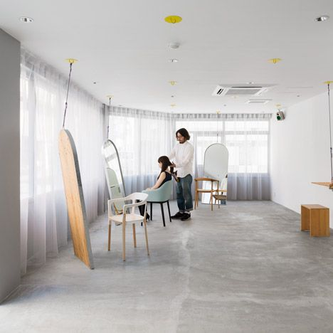 This small hair salon in Osaka, Japan has a series of ceiling hooks that allow the owner to rearrange the mirrors and shelves that help define the space.