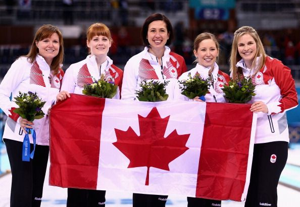 Gold medalists Jennifer Jones (R), Kaitlyn Lawes (2nd R), Jill Officer (C), Dawn McEwen (2nd L) and Kirsten Wall (L) of Canada celebrate during the flower ceremony for the Gold medal match between Sweden and Canada (c) Getty Images