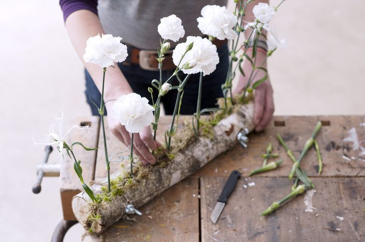 The contrast of white carnations against the tree bark creates a striking effect.