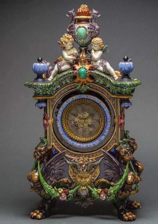 FINE CONTINENTAL POLYCHROMED MAJOLICA RENAISSANCE INSPIRED MANTEL CLOCK circa 1870 unmarked, surmounted by two putti dotted with foliage and hung with garlands, the base with a bearded satyr mask flanked by acanthus and hung with fruited festoons, on four shaped legs ending in paws Height 23 ½ in., Width 13 in., Depth 8 in.