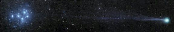 Comet Lovejoy flashes through the darkness of the Solar System, passing near the open star cluster of the Pleiades or Seven Sisters. The Pleiades glow blue due to their extremely hot nature, and are the most obvious star cluster to the naked eye in the night sky