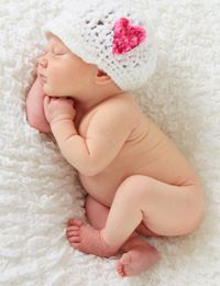 Newborn baby girl asleep on a blanket. This image is also available