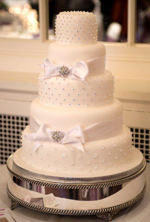 gâteau de mariage blanc décoré de noeuds et perles brillantes