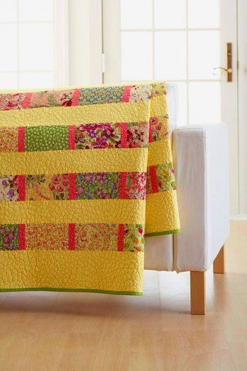 Fat Quarter Twin Bed Quilt - Cut rectangles from floral fat quarters and join them with solid watermelon pink strips to create pieced rows. Show off your machine-quilting abilities in the solid yellow sashing strips in this simple, yet stunning twin-bed quilt.